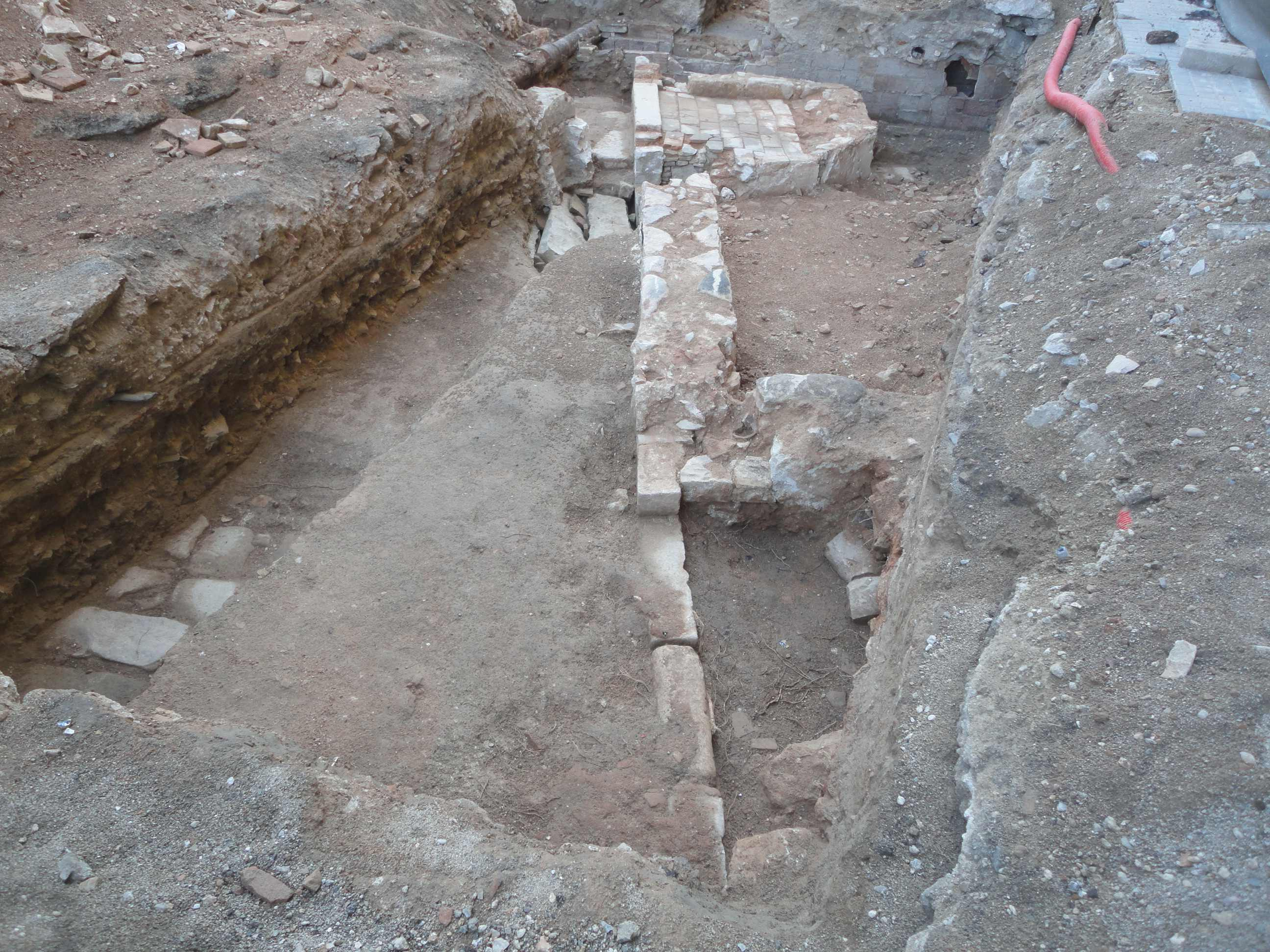 Àmbit actualment en procés d'excavació. A l'esquerra del mur de façana hi ha l'enllosat del carrer i, a la dreta, l'interior de l'edifici. Foto: Sergio Arroyo