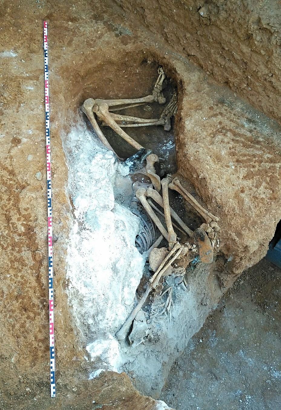 Detall del procés d'excavació de les dues inhumacions amb la capa de calç viva que les cobria. Foto: Esther Medina