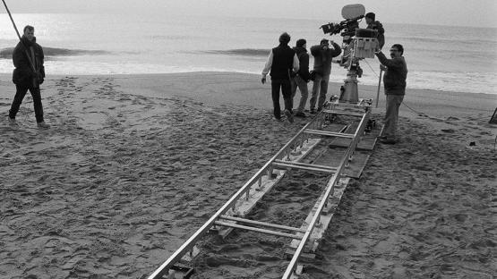 Foto en blanc i negre. Es veu el director de cine rodant una escena a la platja
