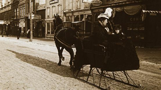 Es veu trineu ocupat per una senyora i arrossegat per un cavall, per un carrer de Winnipeg. Canadà