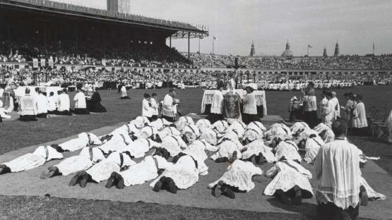 Black and white photo of the ordination ceremony of new priests, lying on the floor at Montjuïc stadium