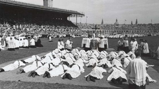 Foto en blanco y negro de la ceremónia de ordenación de nuevos sacerdotes, estirados en el suelo del Estadio de Montjuïc