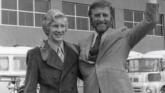 Foto en blanco y negro que retrata al actor Kirk Douglas y su hijo Peter en frente de l'aeroport del Prat. El actor saluda y sonrie