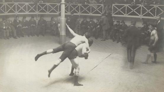 Foto en blanc i negre, públic en cercle i dos homes fent lluita grecorromana al centre