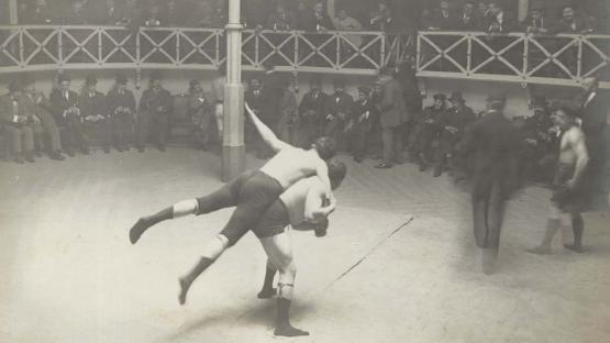 Foto en blanco y negro, público en círculo y dos hombres haciendo lucha grecorromana en el centro
