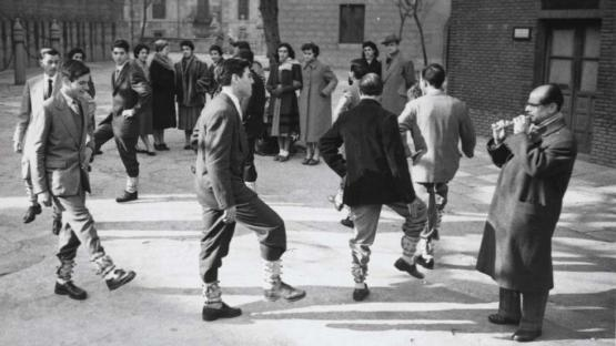 """Foto en blanco y negro de jóvenes en círculo haciendo el baile de """"Els Picarols"""", una danza popular"""