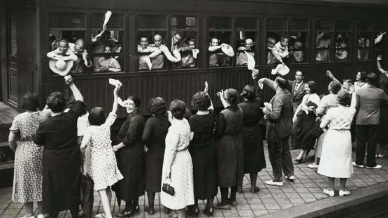 Foto en blanc i negre de nens abocats a les finestres del tren acomiadant dels seus familiars de l'andana