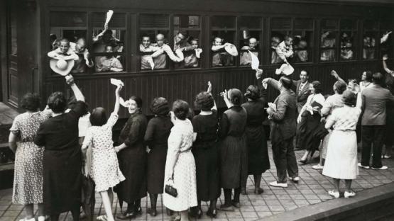 Foto en blanco y negro de niños asomados a las ventanas del tren despidiéndose de sus familiares del andén