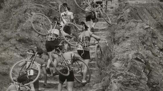 Foto en blanco y negro de ciclistas que llevan bicicletas en la espalda para subir una colina durante el Campeonato de Cataluña de peatones de Cross-cycle. Atajo de Vallvidrera
