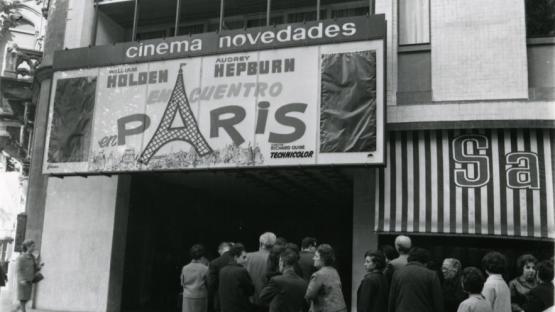 Foto en blanco y negro de la entrada del cine Novedades con gente haciendo cola en la puerta