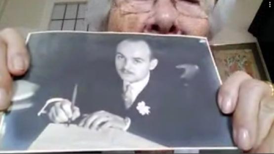 Es veu una iaia que ensenya una foto familiar des de la pantalla del seu ordinador