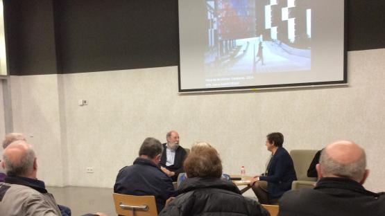 Foto en color. Es veuen 2 conferenciants i public escoltant en una sala