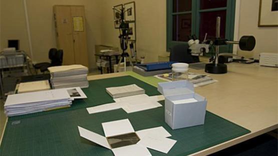 Foto a color. Es veu el laboratori de conservació amb material fotogràfic de conservació damunt una taula de treball
