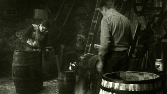Foto en blanc i negre. Es veuen 2 artesans fent botes de vi en el seu taller