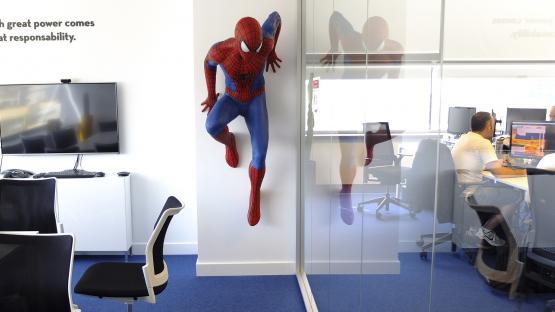 Foto a color. Es veu una oficina moderna amb molta llum natural, gent treballant i a la paret sobresortint una figura de comic tamany natural