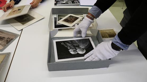 Foto a color. Es veu persona amb guants blancs manipulant una foto dels fons de l Arxiu Fotogràfic