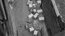 Foto en blanco y  negro. Vista de la calle Carabassa desde el terrado  con cajas de madera grandes . Un hombre sentado sobre una caja y un niño jugando