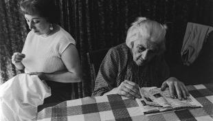 Foto en blanc i negre. Es veu una escena amb una senyora cosint i una iaia llegint revista