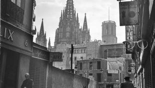 Foto en blanc i negre. Es veu el carrer dels Arcs amb la Catedral al fons i gent caminant