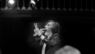 Foto en blanc i negre. El director d orquestra Oriol Martorell dirigint als músics