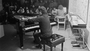 Foto en blanc i negre. Es veu el músic Carles Santos davant del piano actuant
