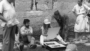 Es veuen fotògrafs asseguts al terra  visionant els seus treballs