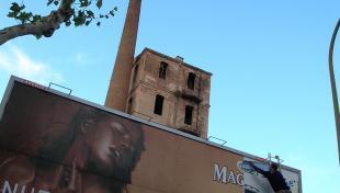 Foto a color. Es veu en primer terme una tanca publicitària amb un anunci de xocolata i al darrera la silueta d'una fàbrica amb la xemeneia