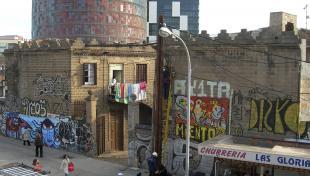Foto en color. Es veu una xurreria i gent caminant i al darrera edifici antic i molts cables de llum penjant i al fons la torre Agbar