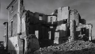 Foto en blanc i negre. Es veu edifici en runes, amb algunes parets caigudes i sense teulada