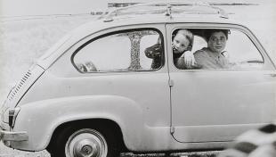 Foto en blanc i negre. Es veu un cotxe model Sis-cents amb mare i filla a dins mirant per la finestra
