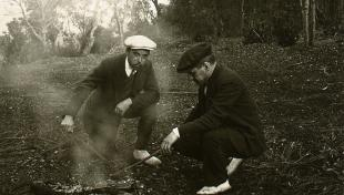 Foto en blanc i negre. Es veuen 2 senyors fent una foguera al bosc