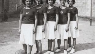 Foto en blanc i negre de cinc jugadores de l'equip de bàsquet de Gràcia posant