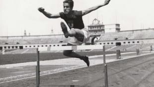 """Foto en blanc i negre del guanyador de la cursa """"Fumador"""", en acció durant els 110 metres d'obstacles del Campionat de Catalunya"""