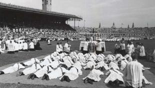 Foto en blanc i negre de la ceremonia d'ordenació de nous sacerdots estirats a terra a l'estadi de Montjuïc