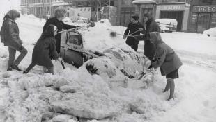 Foto en blanc i negre. Es veu un grup de 6 persones molt abrigades  treien neu de damunt de cotxe que està sepultat per la neu caiguda
