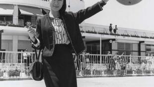 La foto en blanc i negre que retrata l'actriu xinesa Tiny Young a la seva arribada a l'aeroport, té un barret tradicional xinès a la mà