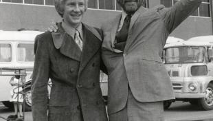 Foto en blanc i negre. Retrat de l'actor Kirk Douglas i el seu fill Peter davant l'aeroport del Prat. L'actor està saludant i somrient