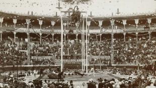 Foto en blanc i negre de l'espectacle del circ eqüestre a Les Arenes ple de públic
