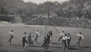 """Foto en blanc i negre de joves en rotllana fent el """"Ball de Gitanes"""" al Parc Güell, una dansa popular"""