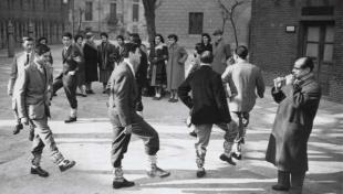 """Foto en blanc i negre de joves en rotllana fent el """"Ball dels Picarols"""", una dansa tradicional"""