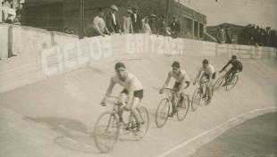 Foto en blanc i negre de quatre ciclistes a les sis hores de la cursa ciclista de Sants