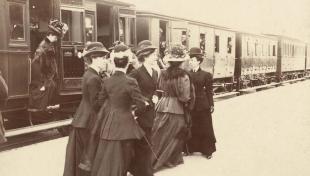 Foto en blanc i negre de l'arribada amb tren de set dones