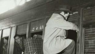 Foto en blanc i negre d'home entrant al tren per la finestra del tren a L'estació de França