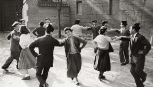 """Foto en blanc i negre de joves ballant en parelles el """"Patatuf de Viladecans"""" al Poble Espanyol, una dansa popular"""