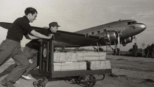 Foto en blanc i negre de dos treballadors empenyent un carro carregat de seda cap a un avió amb destinació a Dublín