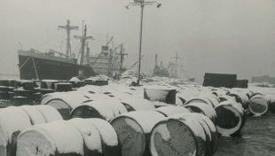 Foto en blanc i negre. Dia molt gris. Es veuen vaixells de càrrega i en primer terme bidons plens de neu pel damunt