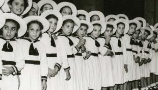 Foto en blanco y negro de niñas colocadas en línea, vestidas de blanco en la procesión de La Merced