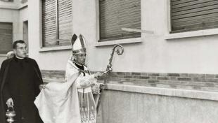 Foto en blanco y negro del Obispo auxilar de Vic bendiciendo las casas de Manresa