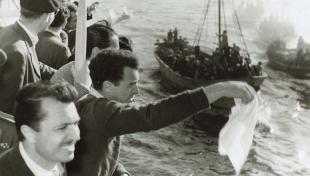 Foto en blanc i negre de l'arribada dels soldats de la División Azul, a bord del vaixell Semiramis, saludant amb un mocador