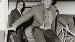 Foto en blanc i negre, retrat de Danny Kaye baixant les escales de l'avió a l' arribada a l'aeroport del Prat